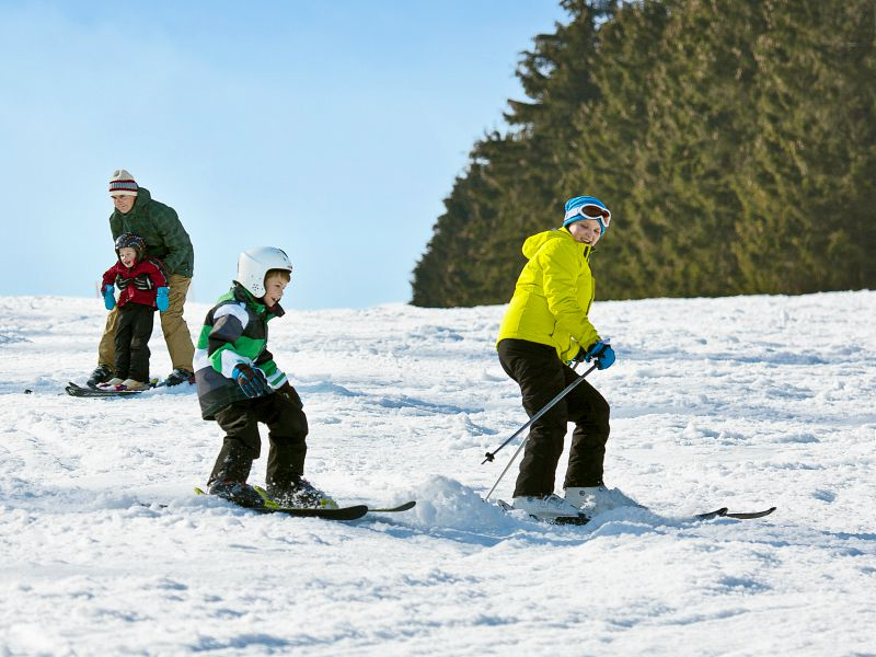 gezin komt op de ski's de berg af