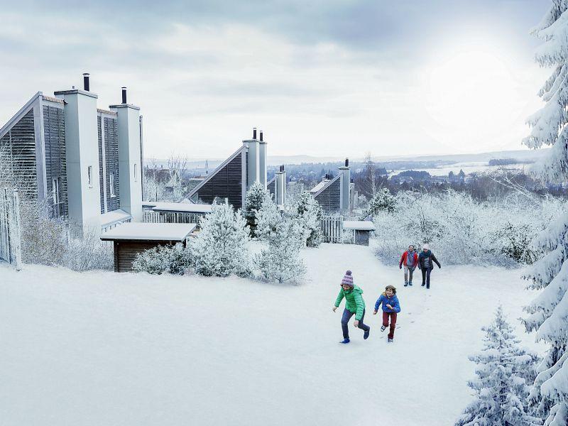 gezin loopt langs de cottages in de sneeuw